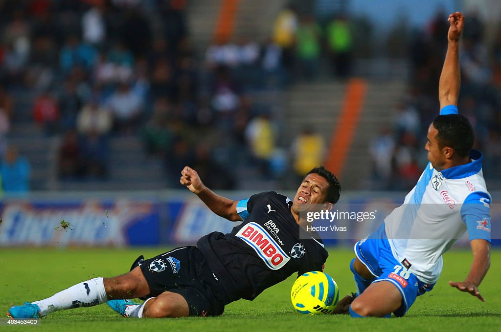 Severo Meza of Monterrey struggles for the ball with Francisco Torres of Puebla during a match between Puebla and Monterrey as part of 6th round...