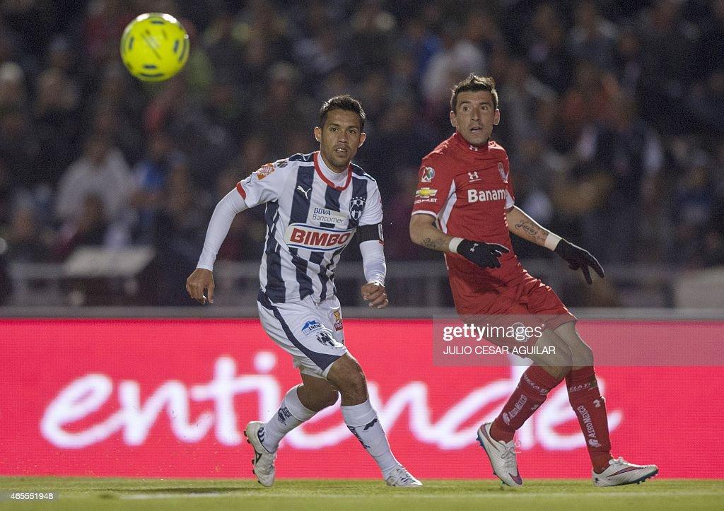 Severo Meza of Monterrey vies for the ball with Edgar Benitez of Toluca during their 2015 Mexican Clausura tournament football match in Monterrey on...