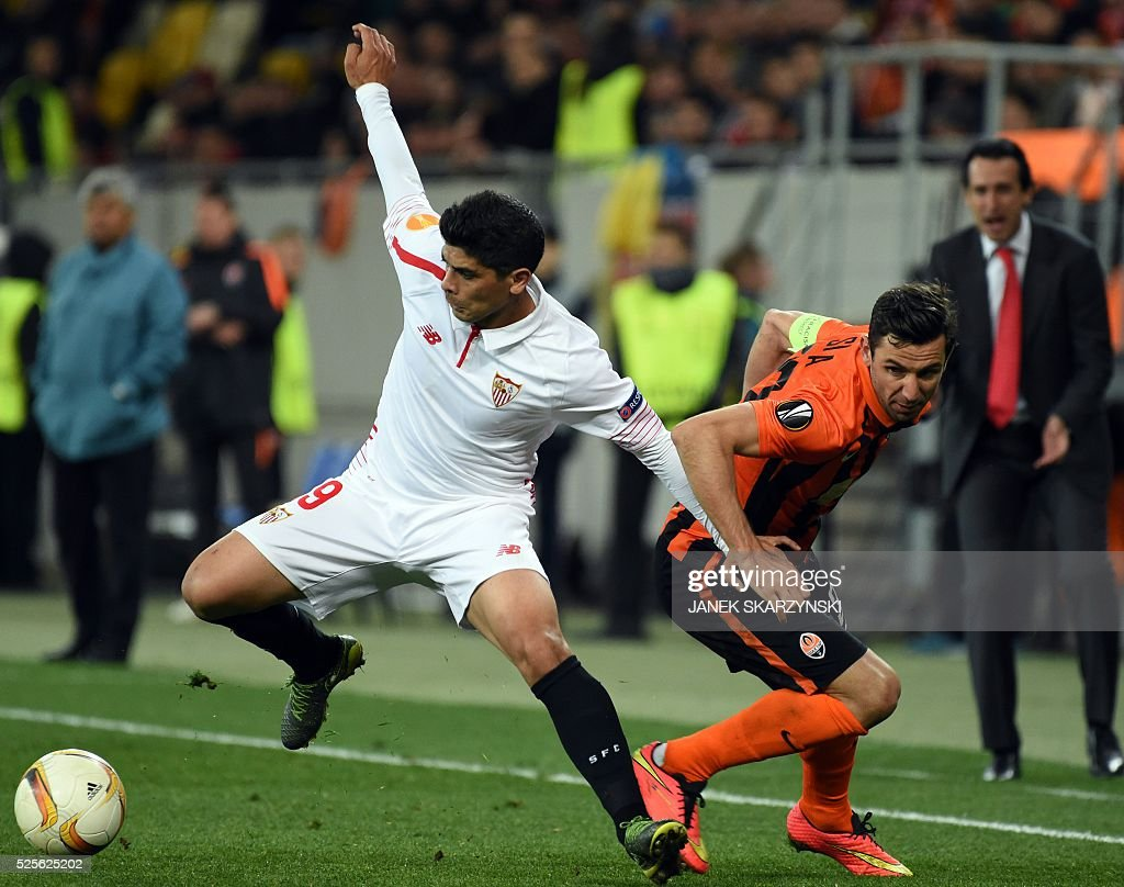Sevilla FC Ever Banega (L) vies for a ball with Shakhtar Donetsk Darijo Srna during the UEFA Europa League semi-final football match FC Shakhtar Donetsk vs Sevilla FC at the Arena Lviv stadium in Lviv on April 28, 2016. / AFP / JANEK