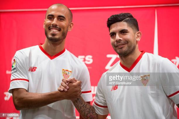 Sevilla FC football team's new players Argentinian midfielder Guido Pizarro and Argentinian midfielder Ever Banega shake hands during their official...
