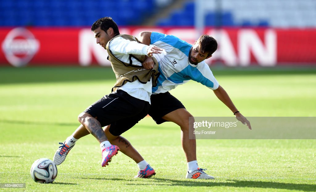 Sevilla FC forward <a gi-track='captionPersonalityLinkClicked' href=/galleries/search?phrase=Jose+Antonio+Reyes+-+Soccer+Player&family=editorial&specificpeople=211507 ng-click='$event.stopPropagation()'>Jose Antonio Reyes</a> is challenged by <a gi-track='captionPersonalityLinkClicked' href=/galleries/search?phrase=Diogo+Figueiras&family=editorial&specificpeople=10127097 ng-click='$event.stopPropagation()'>Diogo Figueiras</a> during Sevilla FC training prior to the UEFA Super Cup match at Cardiff City Stadium on August 11, 2014 in Cardiff, Wales.