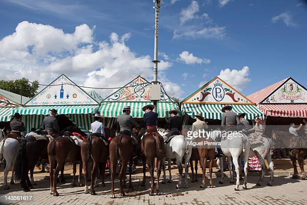'Sevillanos' line up on their horses to get a glass of sherry wine at their stand at the Seville April Fair on April 28 2012 in Seville Spain Dating...