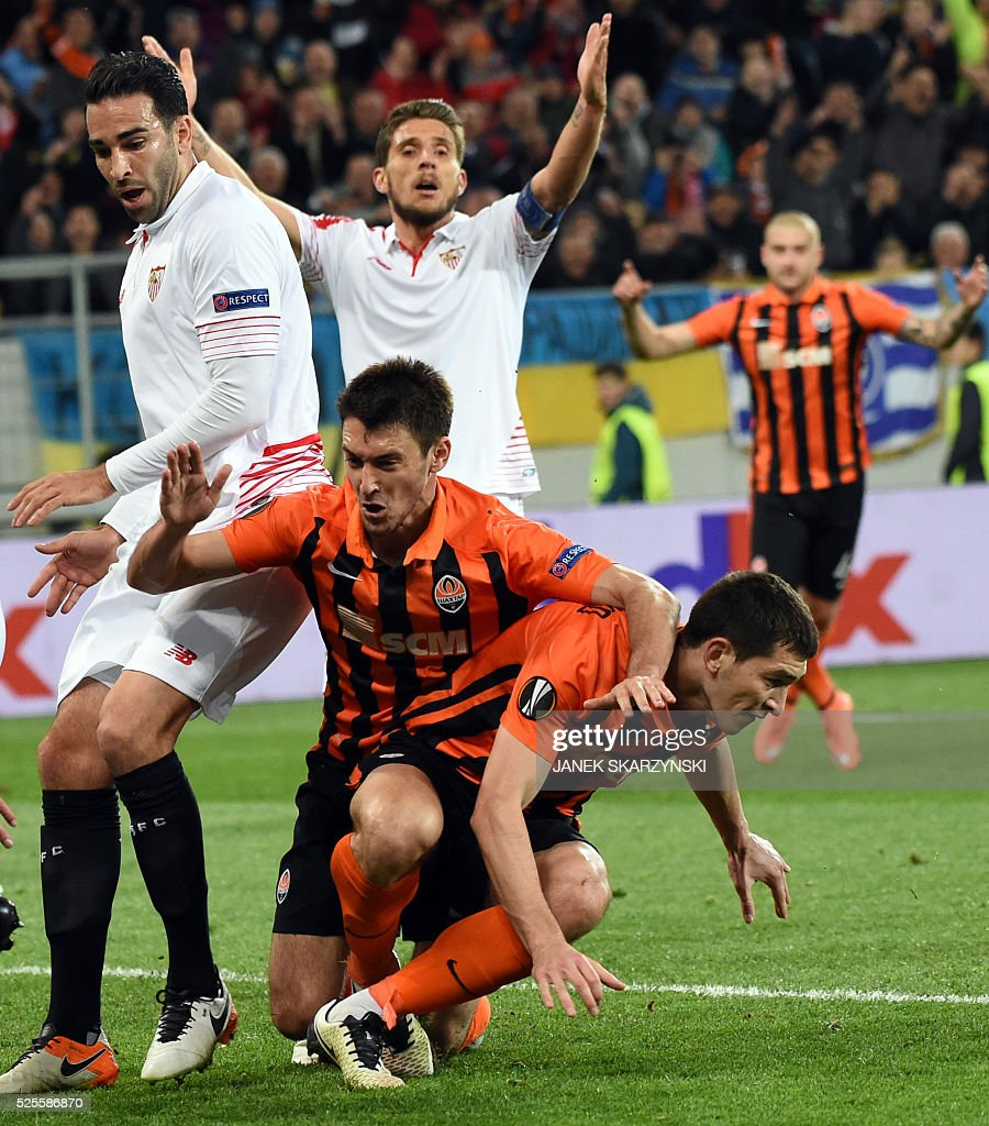 Sevilla's Adil Rami (L) and Daniel Carrico (2nd L) react after Shakhtar Donetsk Taras Spanenko (R) scored a goal next to Facundo Ferreyra during the UEFA European League, semi-final first leg football match between Sevilla FC and Shakhtar Donetsk at Arena Lviv Stadium in Lviv on April 28, 2016. / AFP / JANEK