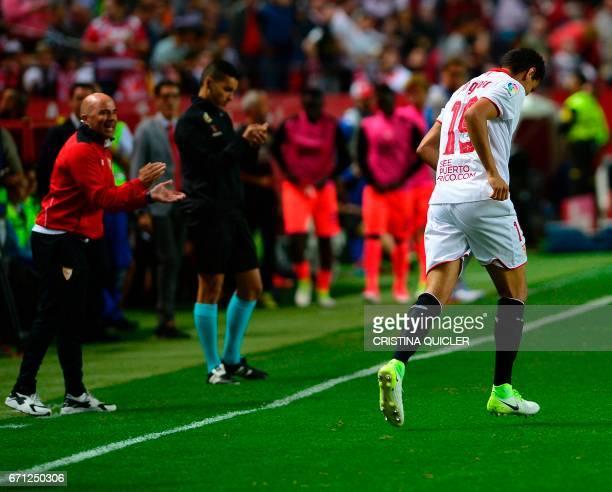 Sevilla's Argentinian coach Jorge Sampaoli applauds Sevilla's Brazilian midfielder Ganso after he scored during the Spanish league football match...