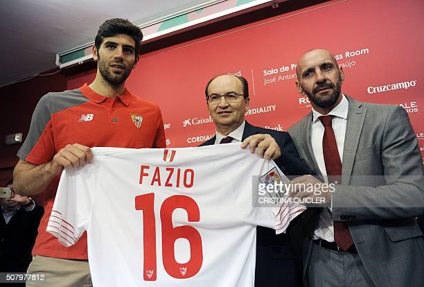 Sevilla's Argentinian defender Federico Fazio poses with with his shirt beside Sevilla's President Jose Castro and sporting director Monchi during...