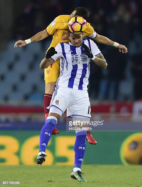 Sevilla's Argentinian defender Nicolas Pareja jumps for the ball with Real Sociedad's Brazilian forward Willian Jose during the Spanish league...