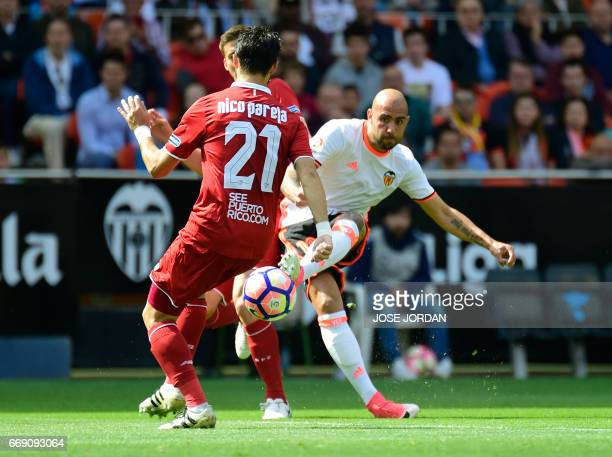 Sevilla's Argentinian defender Nicolas Pareja vies with Valencia's Italian forward Simone Zaza during the Spanish league football match Valencia CF...