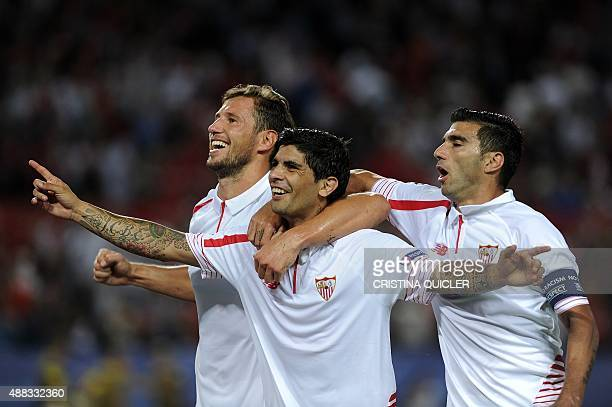 Sevilla's Argentinian midfielder Ever Banega celebrates a goal with teammates Polish midfielder Grzegorz Krychowiak and Spanish forward Jose Antonio...