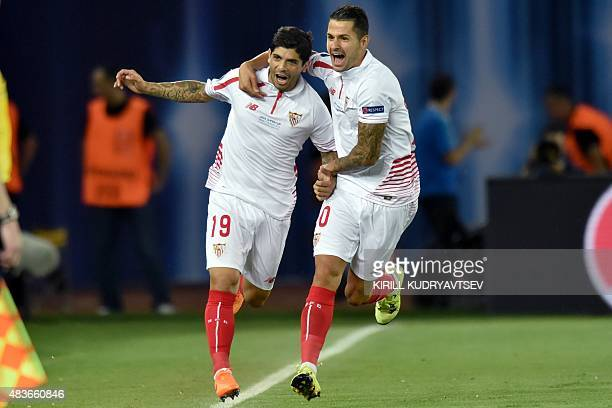 Sevilla's Argentinian midfielder Ever Banega celebrates with Sevilla's midfielder Vitolo after scoring a goal during the UEFA Super Cup final...