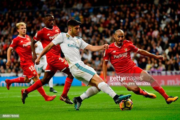 Sevilla's Argentinian midfielder Guido Pizarro challenges Real Madrid's Spanish midfielder Marco Asensio during the Spanish league football match...
