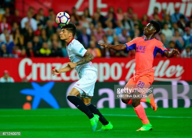 Sevilla's Argentinian midfielder Joaquin Correa heads the ball past Granada's Cameroonian midfielder Martin Hongla during the Spanish league football...