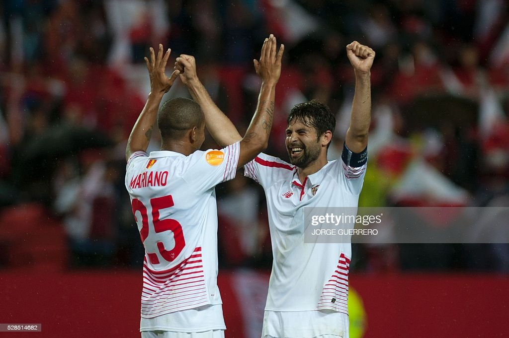 Sevilla's Brazilian defender Mariano Ferreira (L) celebrates with Sevilla's defender Coke their victory over Shakhtar at the end of the UEFA Europa League semi-final second leg football match Sevilla FC vs Shakhtar Donetsk at the Ramon Sanchez Pizjuan stadium in Sevilla on May 5, 2016. Sevilla won 3-1. / AFP / JORGE