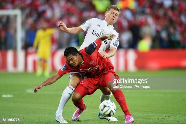 Sevilla's Carlos Bacca is tackled by Real Madrid's Toni Kroos during the UEFA Super Cup Final at the Cardiff City Stadium Cardiff