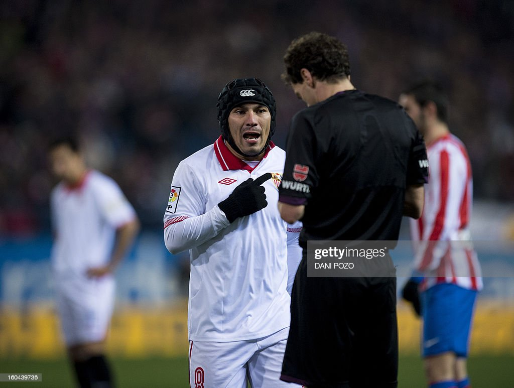Sevilla's Chilean midfielder Gary Medel (L) argues with referee during the Spanish Copa del Rey (King's Cup) semifinal first-leg football match Atletico de Madrid vs Sevilla FC at the Vicente Calderon stadium in Madrid on January 31, 2013.