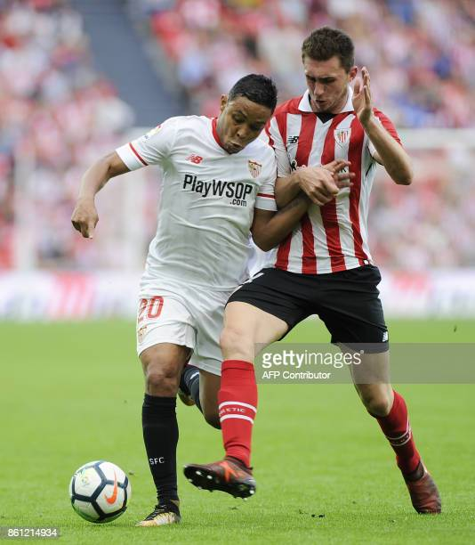 Sevilla's Colombian forward Luis Muriel challenges Athletic Bilbao's French defender Aymeric Laporte during the Spanish league football match...