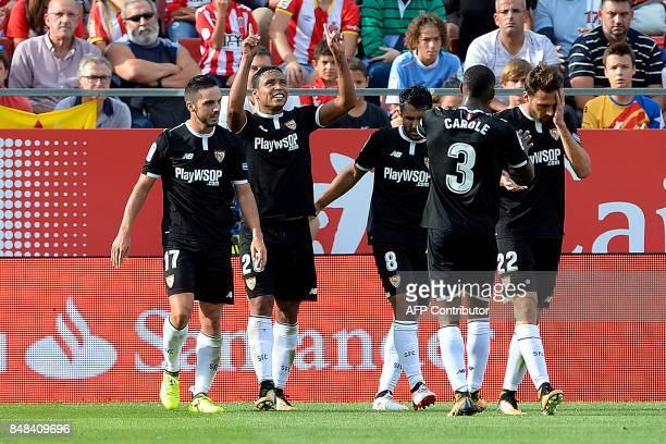 Sevilla's Colombian midfielder Luis Muriel is congratulated by his teammates after scoring during the Spanish league football match Girona FC vs...