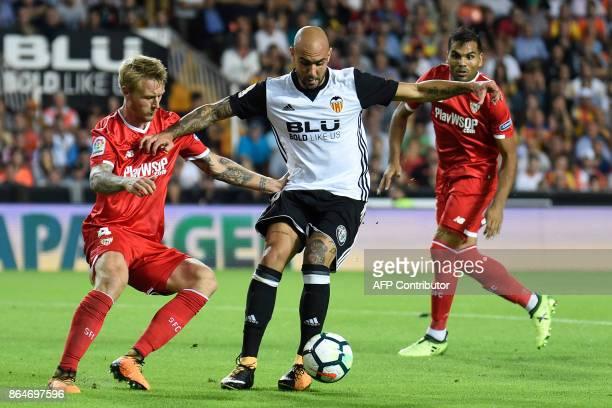 Sevilla's Danish defender Simon Kjaer challenges Valencia's Italian forward Simone Zaza during the Spanish league football match Valencia CF vs...