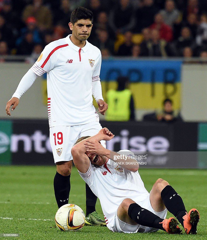 Sevilla's Danish player Michael Krohn-Dehli (R) reacts after being injured, next to his teammate Ever Banega, during the UEFA Europa League semi-final football match FC Shakhtar Donetsk vs Sevilla FC at the Arena Lviv stadium in Lviv on April 28, 2016. / AFP / JANEK