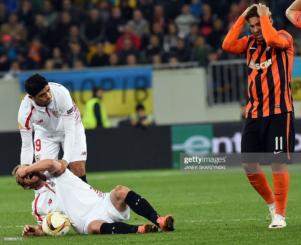 Sevilla's Danish player Michael Krohn-Dehli (R) reacts after being injured, next to his teammate Ever Banega (L) and Shakhtar Donetsk's Ismaily, during the UEFA Europa League semi-final football match FC Shakhtar Donetsk vs Sevilla FC at the Arena Lviv stadium in Lviv on April 28, 2016. / AFP / JANEK