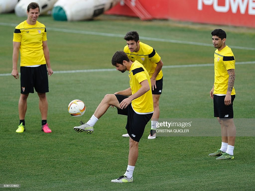 Sevilla's defender Coke (C) controls the ball past his teammates during a training session on May 4, 2016 on the eve of the UEFA Europa League semi-final second leg football match Sevilla FC vs Shakhtar Donetsk at the Ciudad Deportiva in Sevilla. / AFP / CRISTINA