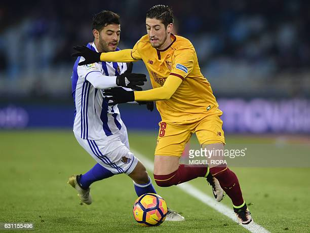 Sevilla's defender Sergio Escudero vies with Real Sociedad's Mexican forward Carlos Vela during the Spanish league football match Real Sociedad vs...