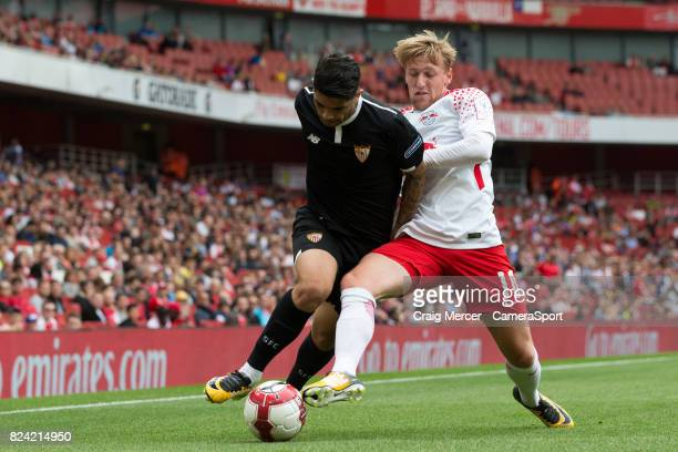 Sevilla's Ever Banega battles for possession with RB Leipzig's Emil Forsberg during the Emirates Cup match between RB Leipzig and Sevilla FC at...