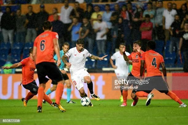 Sevilla's Ever Banega vies for the ball with Basaksehir's Alexandru Epureanu and Joseph Attamah during the UEFA Champions League playoff first leg...