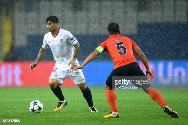 Sevilla's Ever Banega vies for the ball with Basaksehir's Emre Belozoglu during the UEFA Champions League playoff first leg football match between...