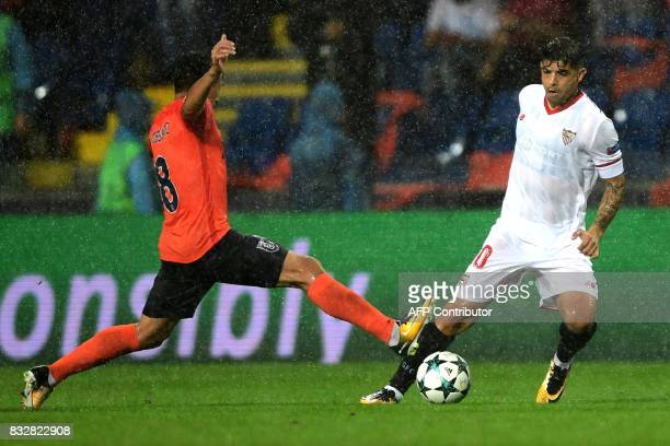 Sevilla's Ever Banega vies for the ball with Basaksehir's Mossoro during the UEFA Champions League playoff first leg football match between Istanbul...