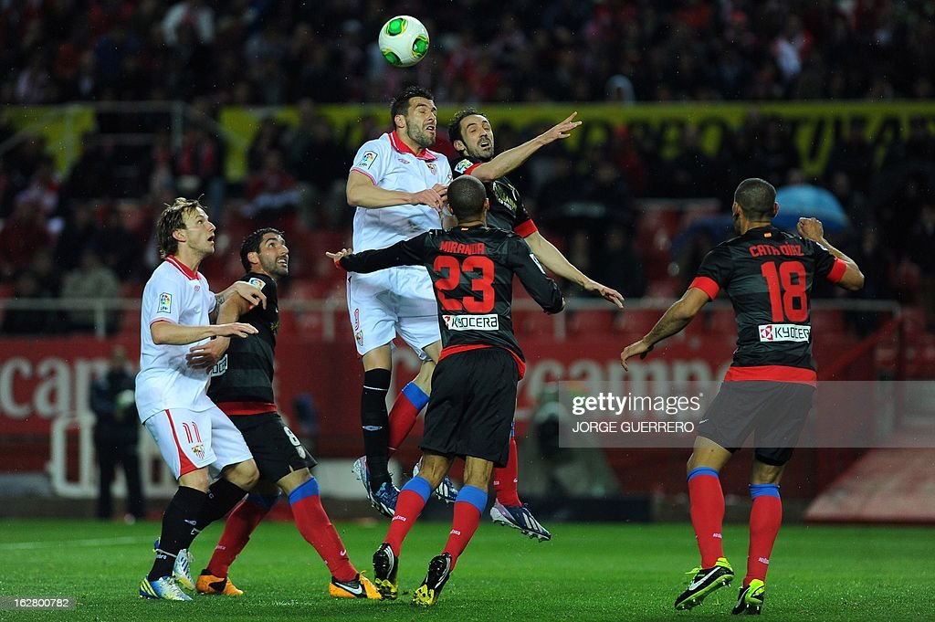 Sevilla's forward Alvaro Negredo (top L) vies with Atletico Madrid's midfielder Juanfran (top R) during the Copa del Rey (King's Cup) semi-final second leg football match Sevilla FC vs Atletico de Madrid at the Ramon Sanchez Pizjuan staduim in Sevilla on February 27, 2013. AFP PHOTO / JORGE GUERRERO