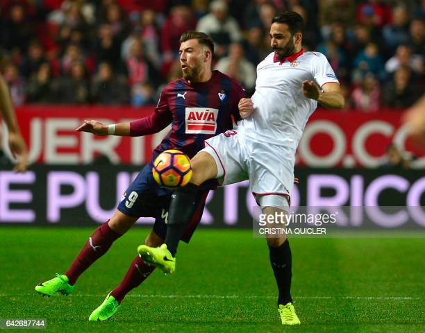 Sevilla's French defender Adil Rami vies for the ball with Eibar's forward Sergi Enrich during the Spanish league football match Sevilla FC vs SD...