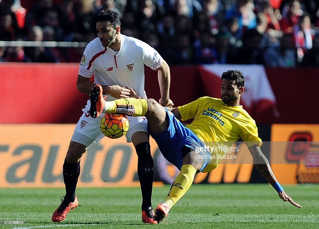 Sevilla's French defender Adil Rami(L) vies with Las Palmas' Brazilian forward Willian Jose (R) during the Spanish league football match FC Sevilla vs UD Las Palmas at the Ramon Sanchez Pizjuan stadium in Sevilla on February 14, 2016. / AFP / CRISTINA QUICLER