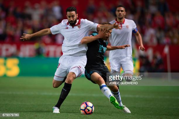 Sevilla's French defender Adil Rami vies with Real Sociedad's midfielder Sergio Canales during the Spanish league football match Sevilla FC vs Real...