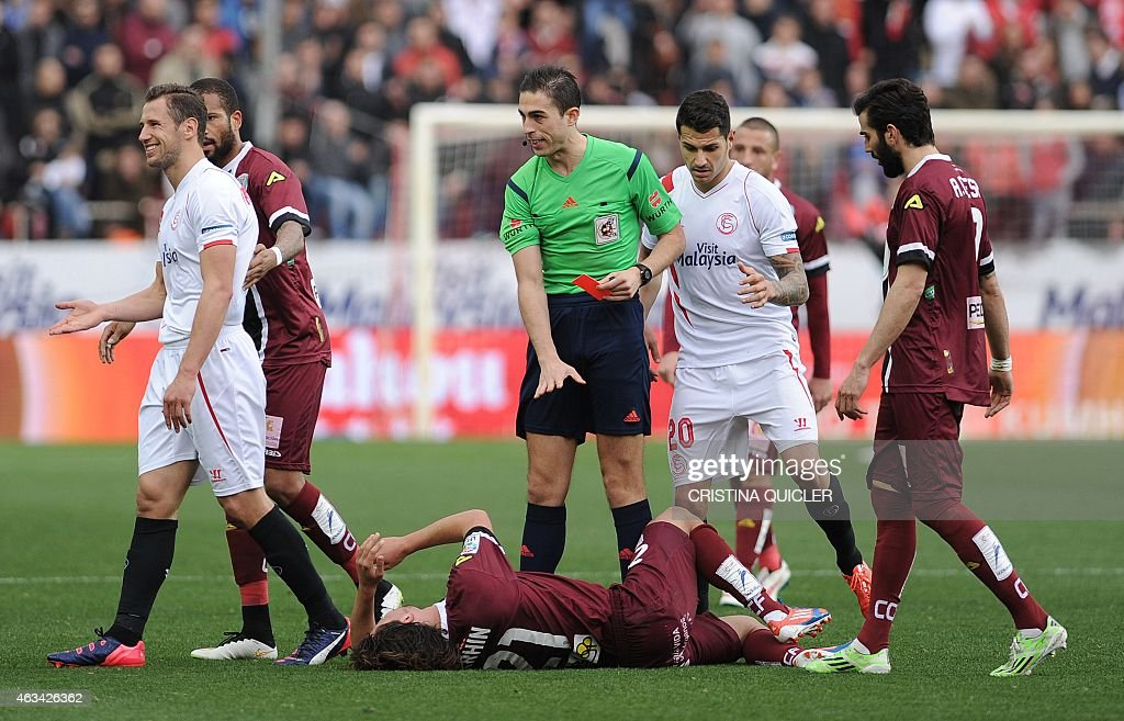 Sevilla's French defender Timothee Kolodziejczak (L) reacts after being shown a red card during the Spanish league football match Sevilla FC vs Cordoba CF at the Ramon Sanchez Pizjuan stadium in Sevilla on February 14, 2015. Sevilla won 3-0.