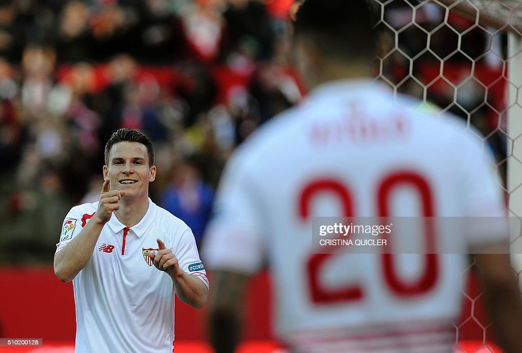 Sevilla's French forward Kevin Gameiro (L) celebrates after scoring during the Spanish league football match FC Sevilla vs UD Las Palmas at the Ramon Sanchez Pizjuan stadium in Sevilla on February 14, 2016. / AFP / CRISTINA QUICLER