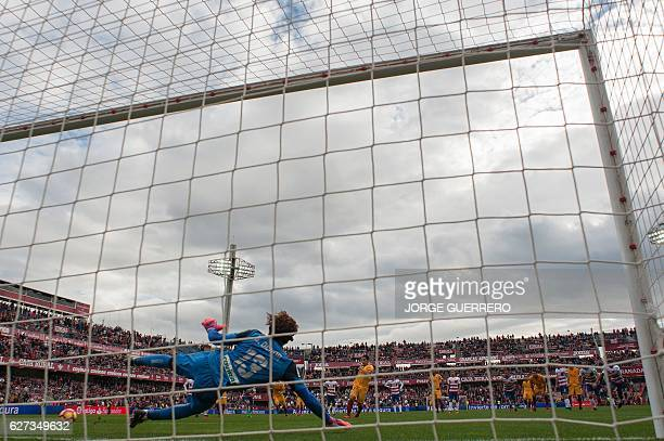 Sevilla's French forward Wissam Ben Yedder shoots a penalty kick to score a goal during the Spanish league football match Granada CF vs Sevilla FC at...