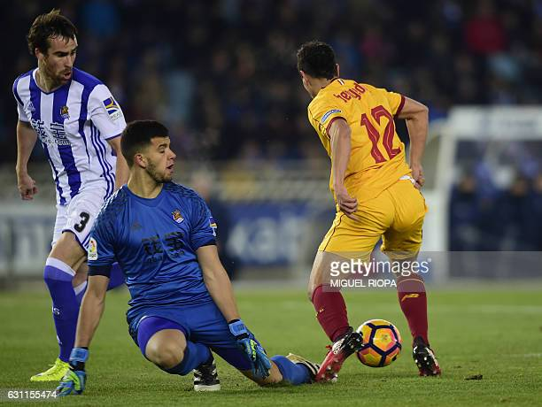 Sevilla's French forward Wissam Ben Yedder vies with Real Sociedad's defender Mikel Gonzalez and Argentinian goalkeeper Geronimo Rulli to score his...