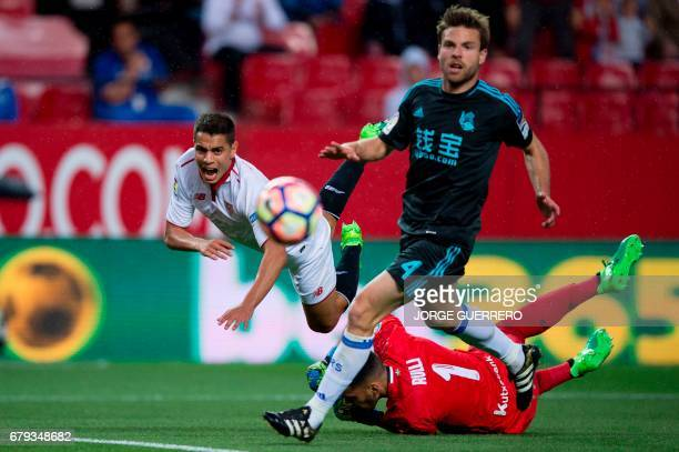 Sevilla's French Tunisian forward Wissam Ben Yedder vies with Real Sociedad's midfielder Asier Illarramendi and Real Sociedad's Argentinian...