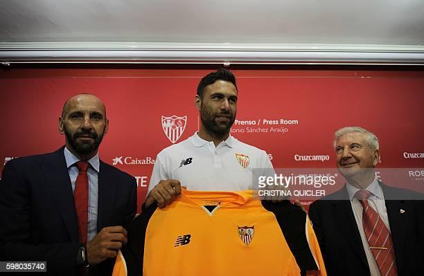 Sevilla's goalkeeper Italian Salvatore Sirigu poses with Sevilla Vice President Gabriel Ramos and Sevilla's Sports Director Monchi during his...