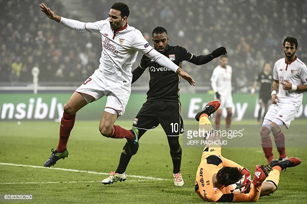 Sevilla's goalkeeper Sergio Rico Gonzalez catches the ball next to Lyon's French forward Alexandre Lacazette and Sevilla's French defender Adil Rami...