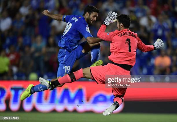 Sevilla's goalkeeper Sergio Rico Gonzalez vies with Getafe's forward Jorge Molina during the Spanish league football match Getafe CF vs Sevilla FC at...