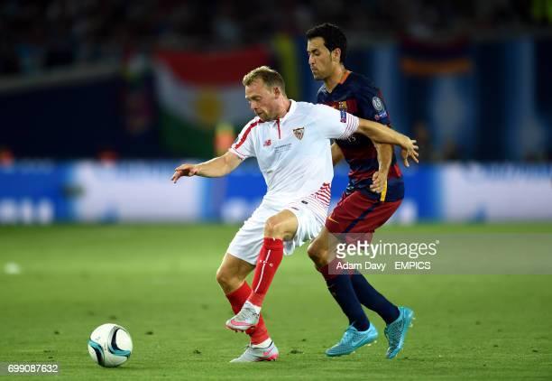 Sevilla's Michael KrohnDehli and Barcelona's Sergio Busquets battle for the ball