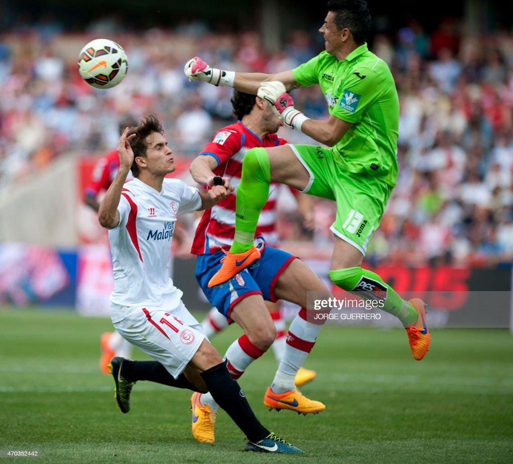 Sevilla's midfielder Denis Suarez vies with Granada's goalkeeper Roberto Fernandez during the Spanish league football match Granada FC v Sevilla FC...