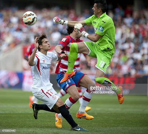 Sevilla's midfielder Denis Suarez vies with Granada's goalkeeper Roberto Fernandez during the Spanish league football match Granada FC v Sevilla FC...