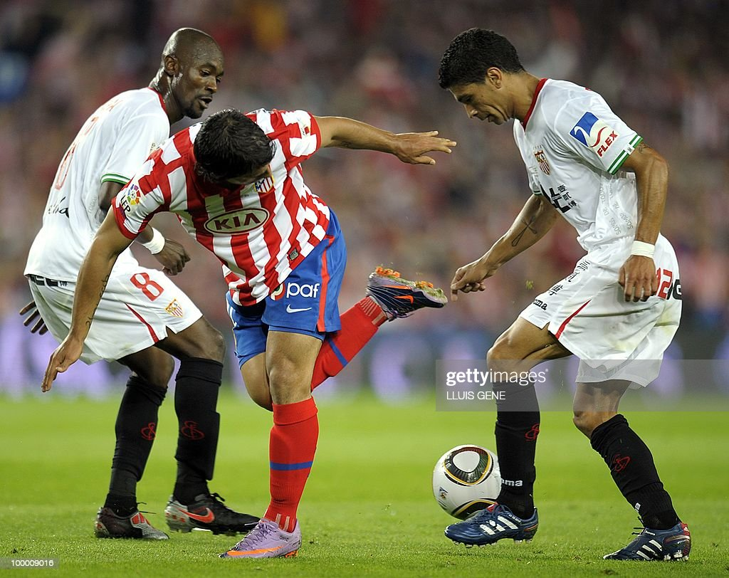Sevilla's midfielder from Ivory Coast Didier Zokora (L) and Sevilla's Brazilian midfielder Renato (R) vie with Atletico Madrid's Argentinian forward Sergio Aguero (C) during the King�s Cup final match Sevilla against Atletico Madrid at the Camp Nou stadium in Barcelona on May 19, 2010.