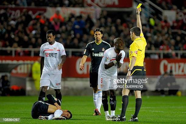 Sevilla's midfielder from Ivory coast Didier Zokora is shown a yellow card as he complains to referee Alberto Undiano after he fouled Real Madrid's...