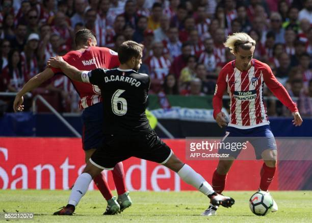Sevilla's midfielder from Portugal Daniel Carrico vies with Atletico Madrid's midfielder from Spain Koke and Atletico Madrid's forward from France...