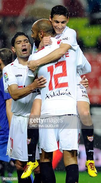 Sevilla's midfielder Jesus Navas celebrates after scoring against Getafe with Sevilla's Malian forward Frederic Kanoute and Sevilla's Brazilian...