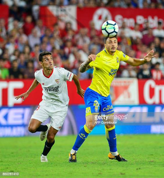 Sevilla's midfielder Jesus Navas fights for the ball with Las Palmas' defender Ximo Navarro during the Spanish league football match Sevilla FC...