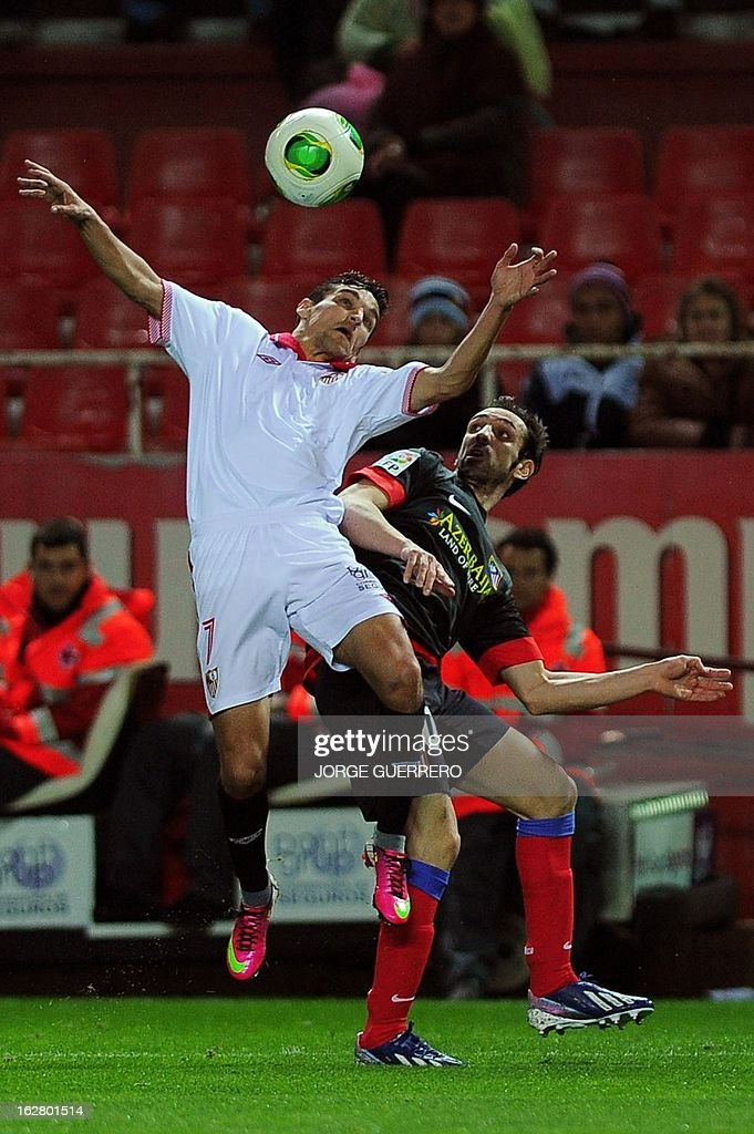 Sevilla's midfielder Jesus Navas (L) vies with Atletico Madrid's midfielder Juanfran during the Copa del Rey (King's Cup) semi-final second leg football match Sevilla FC vs Atletico de Madrid at the Ramon Sanchez Pizjuan staduim in Sevilla on February 27, 2013.